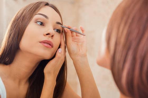 眉毛を処理している女性