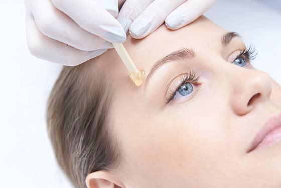 眉毛にワックスを塗られる女性