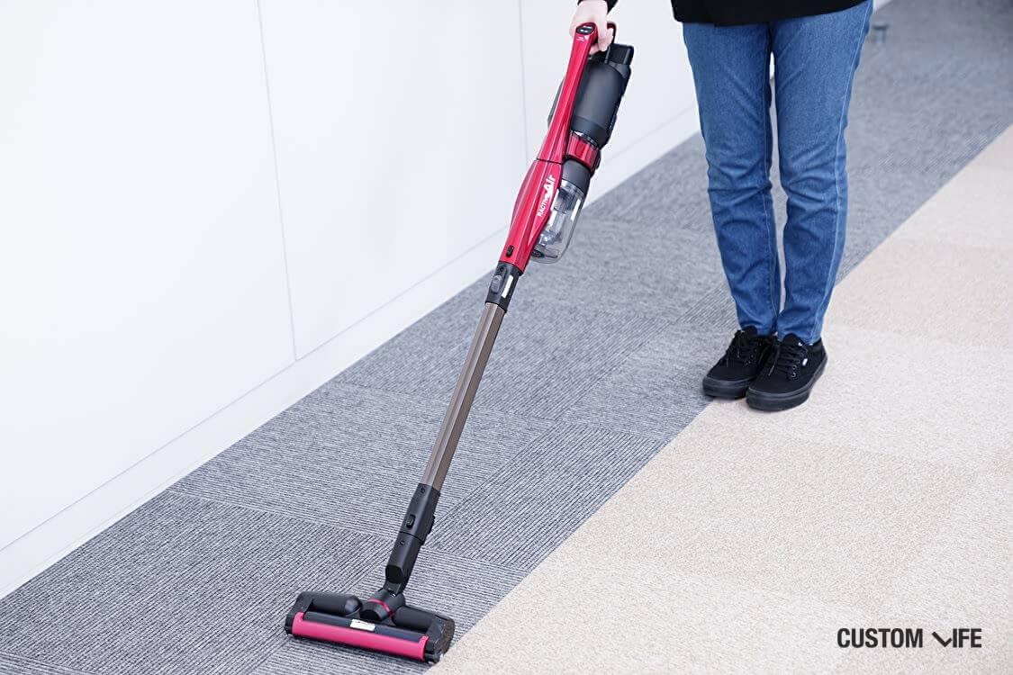 女性が掃除機をかけている場面
