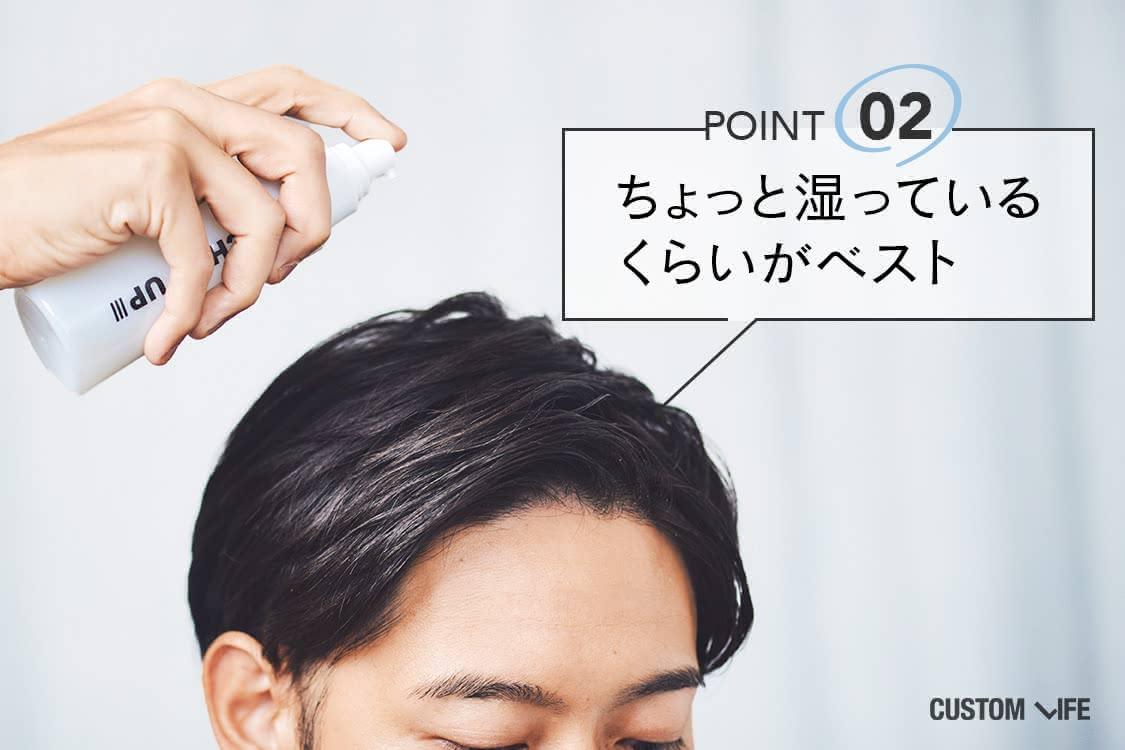 育毛剤を頭皮にスプレーする男性